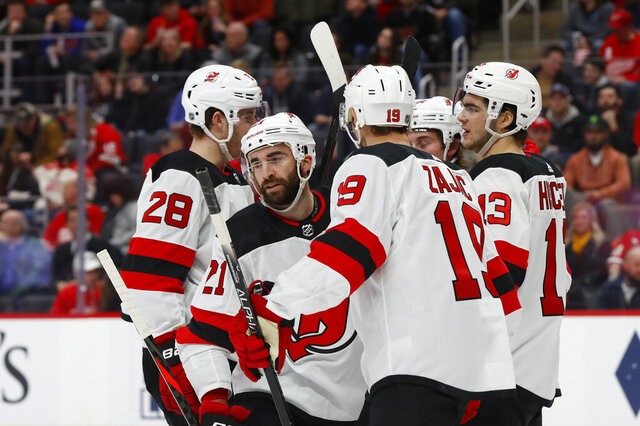 New Jersey Devils right wing Kyle Palmieri (21) celebrates his goal with Damon Severson (28), Travis Zajac (19), and Nico Hischier (13) in the second period of an NHL hockey game against the Detroit Red Wings, Tuesday, Feb. 25, 2020, in Detroit. (AP Photo/Paul Sancya)