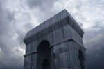 """The wrapped Arc de Triomphe monument is pictured on Saturday, Sept. 18, 2021, in Paris. The """"Arc de Triomphe, Wrapped"""" project by late artist Christo and Jeanne-Claude is on view until Oct. 3. Visitors to the famous Napoleonic arch, which dominates the Champs-Elysees Avenue, will not only be able to see the gleaming silver and blue fabric, but to touch it too — as the artists had intended. (AP Photo/Lewis Joly)"""