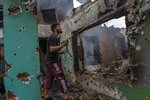 A Kashmiri villager sprays water on burning debris as he clears the house destroyed in a gunfight in Pulwama, south of Srinagar, Indian controlled Kashmir, Wednesday, July 14, 2021. Three suspected rebels were killed in a gunfight in Indian-controlled Kashmir on Wednesday, officials said, as violence in the disputed region increased in recent weeks. Two residential houses were also destroyed. (AP Photo/ Dar Yasin)