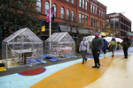 FILE - In this Oct. 18, 2020, file photo, people walk by outdoor plastic dining bubbles on Fulton Market in Chicago. The United States is approaching a record for the number of new daily coronavirus cases in the latest ominous sign about the disease's grip on the nation. (AP Photo/Nam Y. Huh, File)