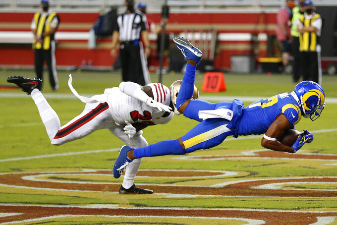 Los Angeles Rams wide receiver Robert Woods, right, catches a touchdown pass in front of San Francisco 49ers strong safety Jaquiski Tartt during the first half of an NFL football game in Santa Clara, Calif., Sunday, Oct. 18, 2020. (AP Photo/Jed Jacobsohn)