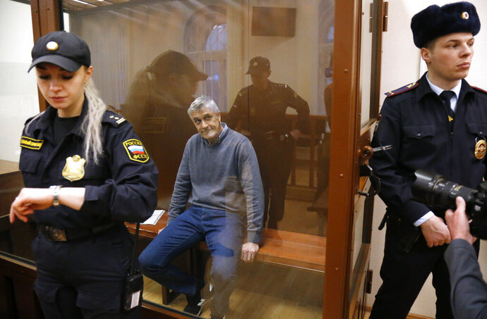 Founder of the Baring Vostok investment fund Michael Calvey sits in a cage in the court room in Moscow, Russia, Friday, Feb. 15, 2019. A veteran U.S. investment fund manager has been detained in Moscow and faces fraud charges. A Moscow court said on Friday that Michael Calvey, founder and senior partner at Baring Vostok equity firm, was detained alongside two other fund managers. (AP Photo/Alexander Zemlianichenko)