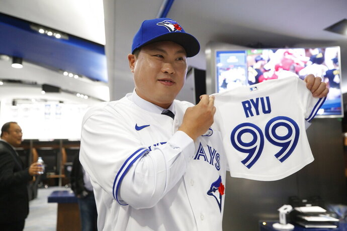 FILE - In this  Friday, Dec. 27, 2019 file photo,Toronto Blue Jays newly signed pitcher Hyun-Jin Ryu holds up a jersey for his expected baby following a news conference announcing his signing to the team in Toronto. Hyun-Jin Ryu is now the clear and undisputed ace of a major league rotation — with all the pressure and responsibility that comes with that. What the Blue Jays need is some stability in their rotation. They used 21 different starters last year, then made several additions in the offseason. Ryu was the most prominent acquisition. (Cole Burston/The Canadian Press via AP, File)