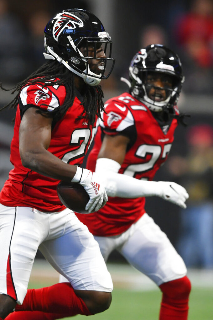 Atlanta Falcons cornerback Desmond Trufant, left, runs the ball after his interception against the Tampa Bay Buccaneers during the first half of an NFL football game, Sunday, Nov. 24, 2019, in Atlanta. (AP Photo/John Amis)