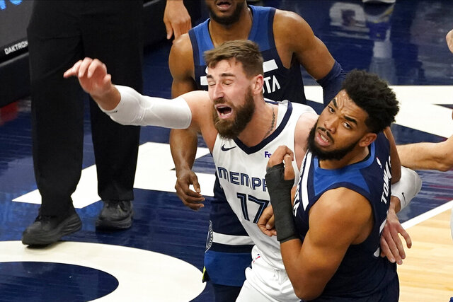 Memphis Grizzlies' Jonas Valanciunas (17) and Minnesota Timberwolves' Karl-Anthony Towns get tangled up in the second half of an NBA basketball game, Wednesday, Jan. 13, 2021, in Minneapolis. The Grizzlies won 118-107. (AP Photo/Jim Mone)