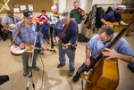 In this Feb. 26, 2016 photo, Dale Bauserman, from left, of Mount Jackson, Va., plays a solo on the Dobro with brothers Roger and Bruce Bynaker, of New Market, Va., during a Friday night bluegrass jam session at the New Market Community Center in New Market, Va. Since March 2020 during the COVID-19 pandemic, musicians have adapted to streaming shows online and collaborating with distant artists for songs in solidarity, but revenue and environmental changes have caused some music makers to reflect on and experiment with their artistic intentions. (Daniel Lin/Daily News-Record via AP)