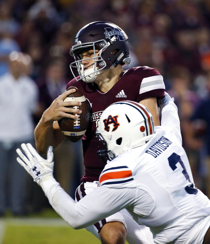 Mississippi State quarterback Nick Fitzgerald (7) avoids a sack by Auburn defensive lineman Marlon Davidson (3) during the first half of their NCAA college football game in Starkville, Miss., Saturday, Oct. 6 2018. (AP Photo/Rogelio V. Solis)