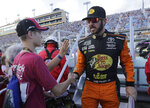Martin Truex Jr. shakes hands with a fan before the NASCAR Cup Series championship auto race at Homestead-Miami Speedway, Sunday, Nov. 18, 2018, in Homestead, Fla. (AP Photo/Lynne Sladky)