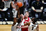 Wisconsin forward Micah Potter (11) goes up for a rebound with Purdue guard Brandon Newman (5) and forward Aaron Wheeler (1) during the first half of an NCAA college basketball game in West Lafayette, Ind., Tuesday, March 2, 2021. (AP Photo/Michael Conroy)