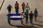 Migrants walk with a Honduran flag, along a highway in hopes of reaching the distant United States, in San Pedro Sula, Honduras, Wednesday, Sept. 30, 2020. Hundreds of migrants have begun walking from this northern Honduras city toward the Guatemala border testing a well-trod migration route now in times of the new coronavirus. (AP Photo)