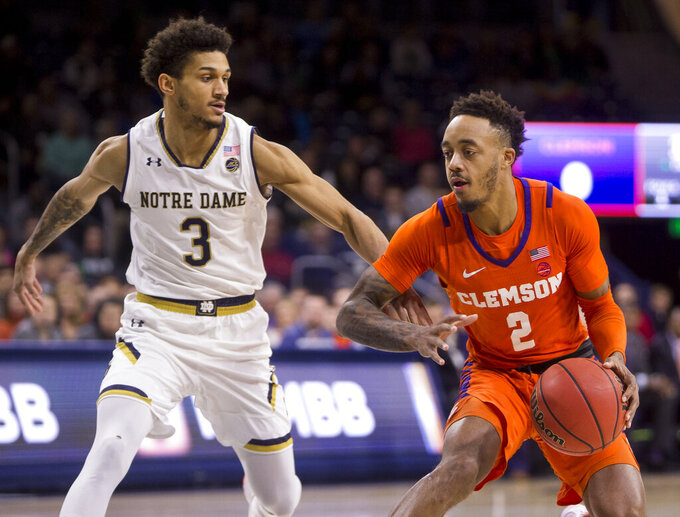Clemson's Marcquise Reed (2) moves by Notre Dame's Prentiss Hubb (3) during the first half of an NCAA college basketball game Wednesday, March 6, 2019, in South Bend, Ind. (AP Photo/Robert Franklin)