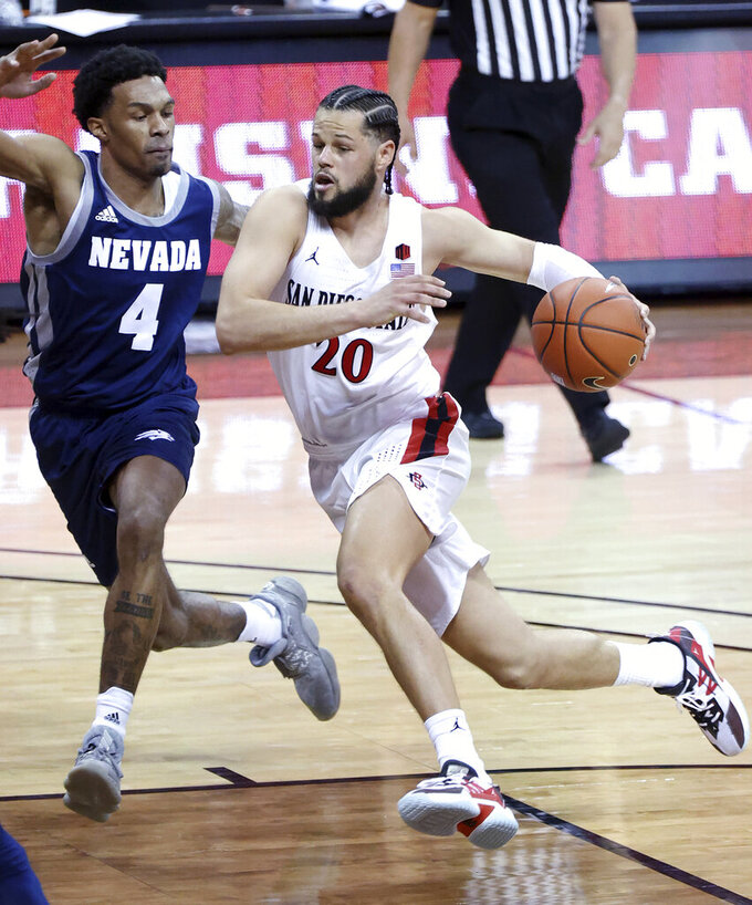 San Diego State guard Jordan Schakel (20) drives as Nevada guard Desmond Cambridge Jr. (4) defends during the second half of an NCAA college basketball game in the semifinals of the Mountain West Conference men's tournament Friday, March 12, 2021, in Las Vegas. (AP Photo/Isaac Brekken)