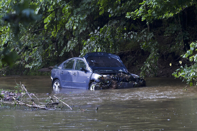 Receding floodwaters of the Manatawny Creek in Boyertown, Pa., Friday, July 12, 2019, reveal the vehicle in which a pregnant woman and young son drowned Thursday after their car was swept from Grist Mill Road in Douglass Township. Emergency workers found the car in a tributary nearly five hours later. The bodies of woman and child were removed on stretchers Thursday, but the car remained in the creek Friday morning. The names of the woman and her son have not been released. (Bill Uhrich/Reading Eagle via AP)