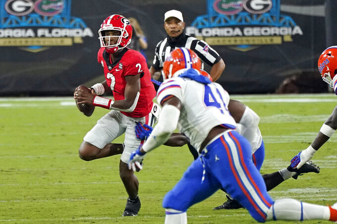 Georgia quarterback D'Wan Mathis (2) looks for a receiver as he is pressured by Florida linebacker James Houston IV (41) during the second half of an NCAA college football game, Saturday, Nov. 7, 2020, in Jacksonville, Fla. (AP Photo/John Raoux)