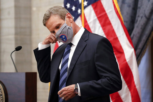 FILE - In this July 1, 2020, file photo, Tennessee Gov. Bill Lee removes his mask as he begins a news conference in Nashville, Tenn. Tennessee was one of the first states to begin reopening in late April after Lee reluctantly issued a safer-at-home order that forced businesses to close. Since then, case numbers have continued to rise in part due to more testing, but also because of an increase in community spread of the disease. (AP Photo/Mark Humphrey, File)