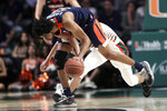Virginia guard Tomas Woldetensae (53) gets a loose ball as Miami guard Isaiah Wong defends during the first half of an NCAA college basketball game, Wednesday, March 4, 2020, in Coral Gables, Fla. (AP Photo/Lynne Sladky)