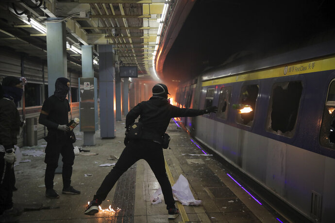 A student hurls a molotov cocktail into a train parked inside the Chinese University MTR station in Hong Kong, Wednesday, Nov. 13, 2019. Protesters in Hong Kong battled police on multiple fronts on Tuesday, from major disruptions during the morning rush hour to a late-night standoff at a prominent university, as the 5-month-old anti-government movement takes an increasingly violent turn. (AP Photo/Kin Cheung)