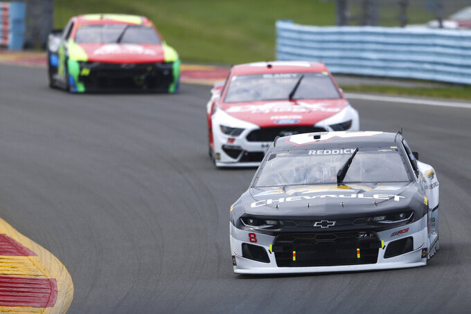 Tyler Reddick (front) turns to the Esses during a NASCAR Cup Series auto race in Watkins Glen, N.Y., on Sunday, Aug. 8, 2021. (AP Photo/Joshua Bessex)