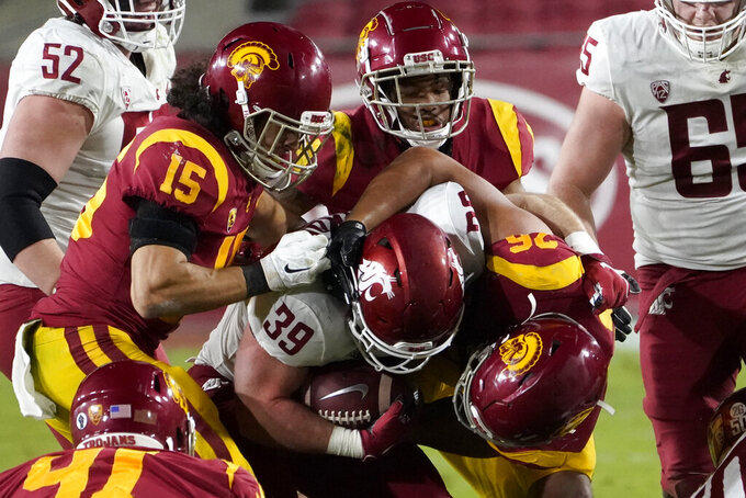 Washington State running back Clay Markof, center, is brought down by Southern California safety Talanoa Hufanga, left, safety Max Williams, top, and linebacker Kana'i Mauga, right, during the second half of an NCAA college football game in Los Angeles, Sunday, Dec. 6, 2020. (AP Photo/Alex Gallardo)