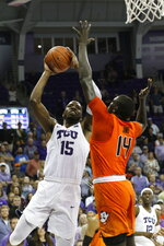 TCU forward JD Miller (15) goes up for the winning shot as Oklahoma State forward Yor Anei (14) defends during an NCAA college basketball game Wednesday, Feb. 6, 2019, in Fort Worth, Texas. (David Kent/Star-Telegram via AP)