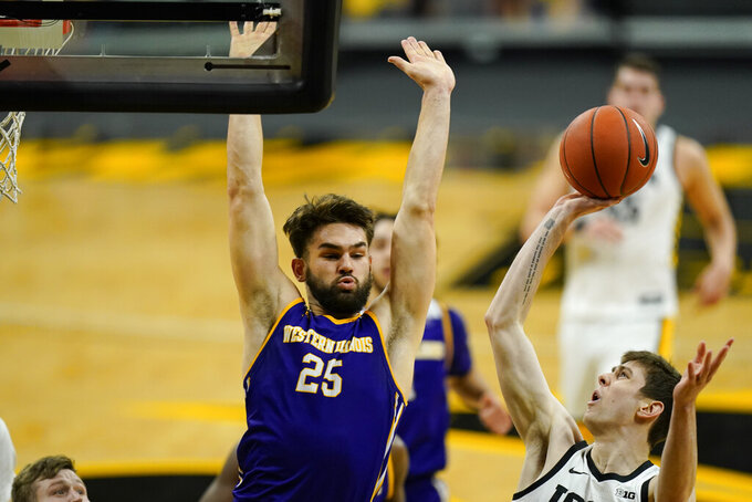 Iowa forward Patrick McCaffery, right, shoots over Western Illinois forward Will Carius, left, during the second half of an NCAA college basketball game, Thursday, Dec. 3, 2020, in Iowa City, Iowa. (AP Photo/Charlie Neibergall)