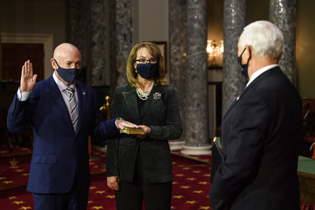 Sen. Mark Kelly, D-Ariz., with his wife former Rep. Gabby Giffords, D-Ariz., participates in a re-enactment of his swearing-in Wednesday, Dec. 2, 2020, by Vice President Mike Pence in the Old Senate Chamber on Capitol Hill in Washington. (Nicholas Kamm/Pool via AP)