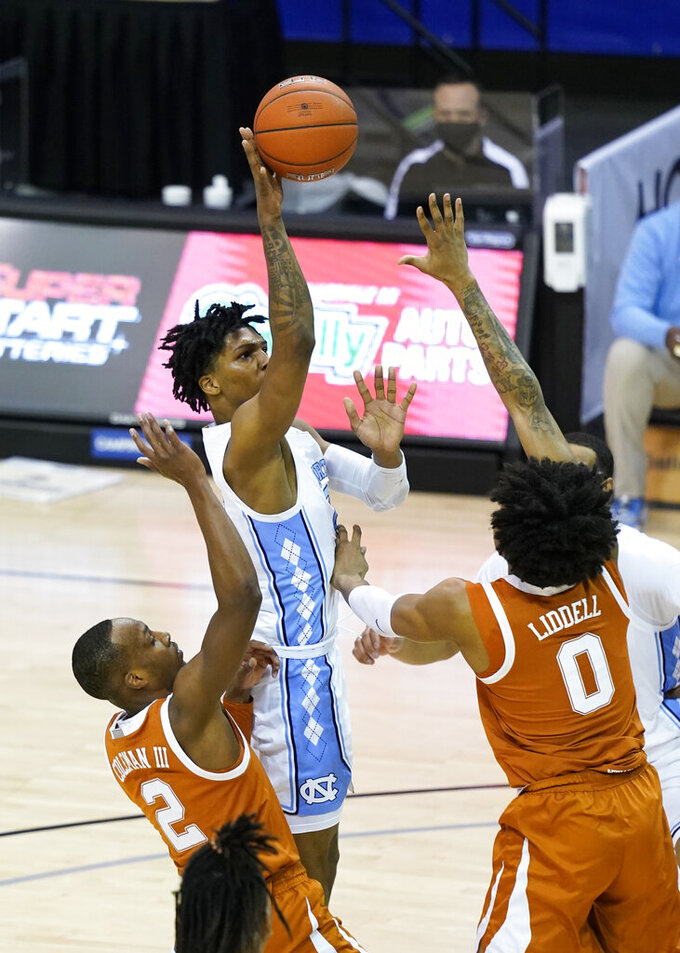 North Carolina guard Caleb Love (2) shoots next to Texas guard Matt Coleman III (2) and forward Gerald Liddell (0) during the second half of an NCAA college basketball game for the championship of the Maui Invitational, Wednesday, Dec. 2, 2020, in Asheville, N.C. (AP Photo/Kathy Kmonicek)