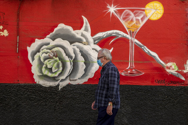 A man wearing a face mask to prevent the spread of coronavirus walks through the Usera neighborhood in Madrid, Spain, Tuesday, Sept. 22, 2020. Madrid is poised to extend its restrictions on movement to more neighborhoods, due to a surge in new cases in other districts and despite an outcry from residents over discrimination. (AP Photo/Manu Fernandez)
