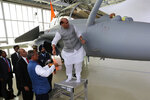 Indian Defense Minister Rajnath Singh has a ritual gesture onto a Rafale jet fighter during an handover cermony at the Dassault Aviation plant in Merignac, near Bordeaux, southwestern France, Tuesday, Oct. 8, 2019. France has delivered to India its first Rafale fighter jet from a series of 36 aircraft purchased in a multi-billion dollar deal in 2016. (AP Photo/Bob Edme)