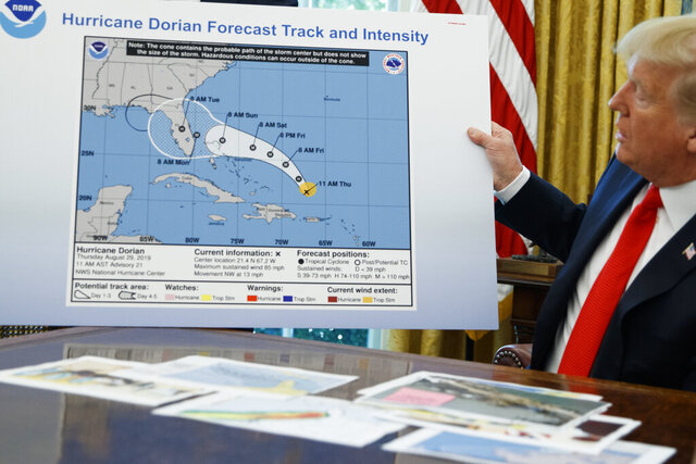 FILE - In this Sept. 4, 2019 file photo, President Donald Trump holds a chart as he talks with reporters after receiving a briefing on Hurricane Dorian in the Oval Office of the White House in Washington. A flurry of newly released emails from scientists and top officials at the federal agency responsible for weather forecasting clearly illustrates the consternation and outright alarm caused by President Donald Trump's false claim that Hurricane Dorian could hit Alabama.  (AP Photo/Evan Vucci)