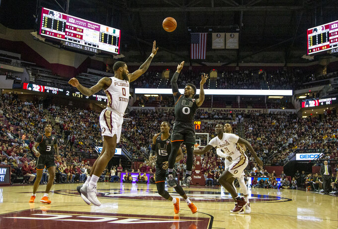 Miami guard Chris Lykes takes a shot on the fast break against Florida State forward Phil Cofer in the first half of an NCAA college basketball game in Tallahassee, Fla., Wednesday, Jan. 9, 2019. (AP Photo/Mark Wallheiser)