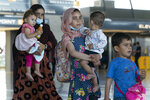 Families evacuated from Kabul, Afghanistan, walk through the terminal before boarding a bus after they arrived at Washington Dulles International Airport, in Chantilly, Va., on Thursday, Sept. 2, 2021. (AP Photo/Jose Luis Magana)