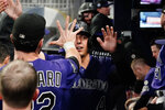 Colorado Rockies' Colton Welker (4) is congratulated by teammates in the dugout after scoring the go-ahead run during the 10th inning of the team's baseball game against the Atlanta Braves on Wednesday, Sept. 15, 2021, in Atlanta. (AP Photo/John Bazemore)