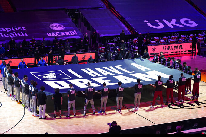 """Miami Heat and Detroit Pistons players hold a """"I Have a Dream"""" banner in honor of the Martin Luther King Jr., holiday before an NBA basketball game, Monday, Jan. 18, 2021, in Miami. (AP Photo/Marta Lavandier)"""