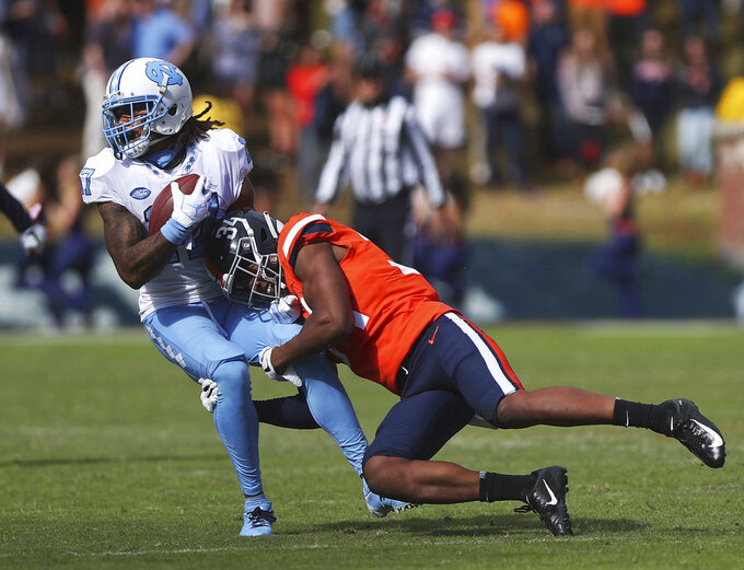 North Carolina's Anthony Ratliff-Williams (17) is tackled by Virginia's cornerback Bryce Hall (34) during the second half of an NCAA college football game on Saturday, Oct. 27, 2018, in Charlottesville, Va. Virginia beat North Carolina 31-21. (Zack Wajsgras /The Daily Progress via AP)