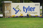 The sign for Tyler Technologies is seen outside the company's offices, Thursday, Sept. 24, 2020, in Plano, Texas. The major U.S. provider of software services to state and local governments, including the online publishing of election results, has told customers that an unknown intruder broke into its phone and IT systems. Plano, Texas-based Tyler Technologies told customers in an email that it discovered the breach and contacted law enforcement and enlisted outside cybersecurity help. (AP Photo/LM Otero)