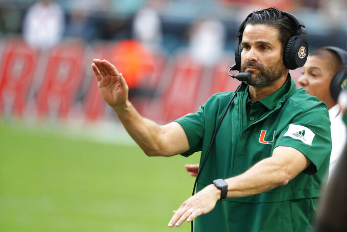 FILE - In this Saturday, Nov. 9, 2019, file photo, Miami head coach Manny Diaz calls out a play during the first half of an NCAA college football game against Louisville in Miami Gardens, Fla. The Hurricanes' head coach — and former defensive coordinator — will call the plays on that side of the football in 2021, he said Thursday, Jan. 14, 2021 while announcing a slew of other changes including the return of Jess Simpson to coach defensive line(AP Photo/Wilfredo Lee, File)