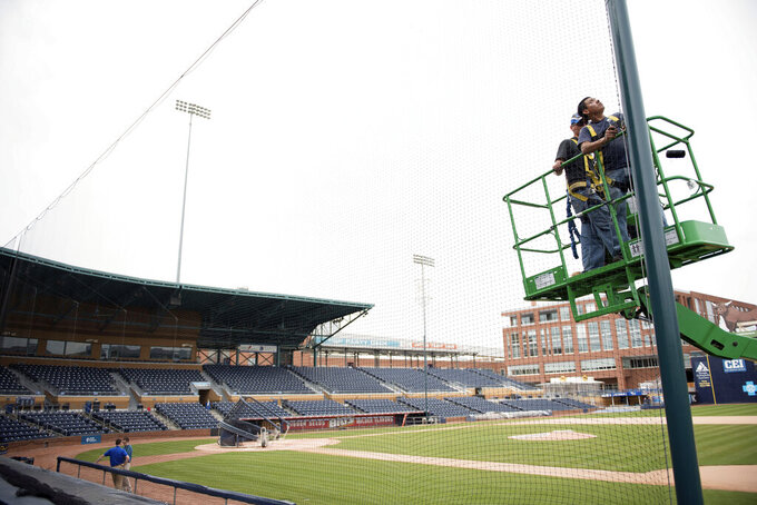 In this March 31, 2016, file photo, Elias Ruiz, front right, and Steven Woytysiak, both from C&H Baseball, help install a 35-foot-high safety netting that runs behind home plate and along the length of each dugout at the Durham Bulls Athletic Park in Durham, N.C. While Major League Baseball tries to figure out a way to play this summer, the prospects for anything resembling a normal minor league season are looking increasingly bleak. For minor league communities across the country, looking forward to cheap hot dogs, fuzzy mascot hugs and various theme nights, it's a small slice of a depressing picture. (Whitney Keller/The Herald-Sun via AP, File)