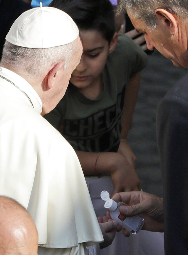 Pope Francis has his hands sanitized by his personal assistant during his weekly general audience general audience in San Damaso courtyard at the Vatican, Wednesday, Sept. 9, 2020. (AP Photo/Andrew Medichini)