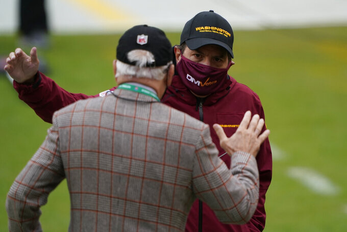 Washington Football Team owner Dan Snyder, right, greeting Dr. James Andrews, left, on the field before the start of an NFL football game, Sunday, Oct. 25, 2020, in Landover, Md. (AP Photo/Susan Walsh)