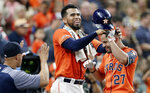 Houston Astros' Robinson Chirinos, center, ruffles Jose Altuve's hair as Altuve heads into the dugout after his home run during the third inning of the team's baseball game against the Texas Rangers on Friday, July 19, 2019, in Houston. (AP Photo/Michael Wyke)