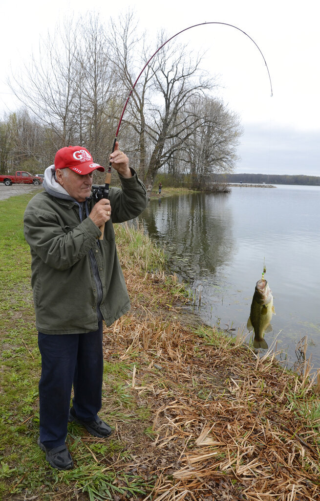 David Batyk holds up a largemouth bass he caught at Mosquito Lake State Park near Cortland, Ohio, Friday, April 16, 2021. A GOP-backed bill introduced Monday, April 19, 2021, would change the name of the state park to honor former President Donald Trump. The House bill primarily sponsored by freshmen Rep. Mike Loychik to rename Mosquito State Park to Donald J. Trump State Park is the latest attempt by Ohio Republicans to honor the former president. (R. Michael Semple/Tribune Chronicle via AP)