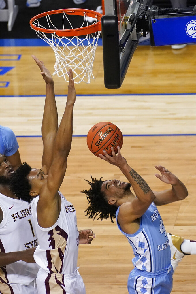 North Carolina guard R.J. Davis (4) tries a shot as Florida State guard Scottie Barnes, left, during the second half of an NCAA college basketball game in the semifinal round of the Atlantic Coast Conference tournament in Greensboro, N.C., Friday, March 12, 2021. (AP Photo/Gerry Broome)