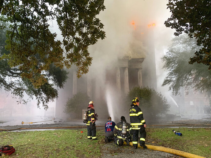 """This photo provided by Columbia Fire Department, firefighters battle a blaze at Babcock Building in Columbia, S.C., on Saturday, Sept. 12, 2020.  Officials said crews were called early Saturday to a three-alarm fire at the Babcock Building, a shuttered former mental asylum that had been planned as part of a luxury housing development. In the fire, the first three-alarm blaze in the city's recent history, Columbia Fire Chief Aubrey Jenkins told reporters the building would likely """"burn to a shell.""""  (Columbia Fire Department via AP)"""