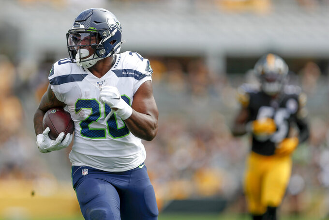 Seattle Seahawks running back Rashaad Penny (20) carries the ball away from Pittsburgh Steelers linebacker Devin Bush (55) on his way to a long touchdown run in the second half of an NFL football game Sunday, Sept. 15, 2019, in Pittsburgh. (AP Photo/Don Wright)