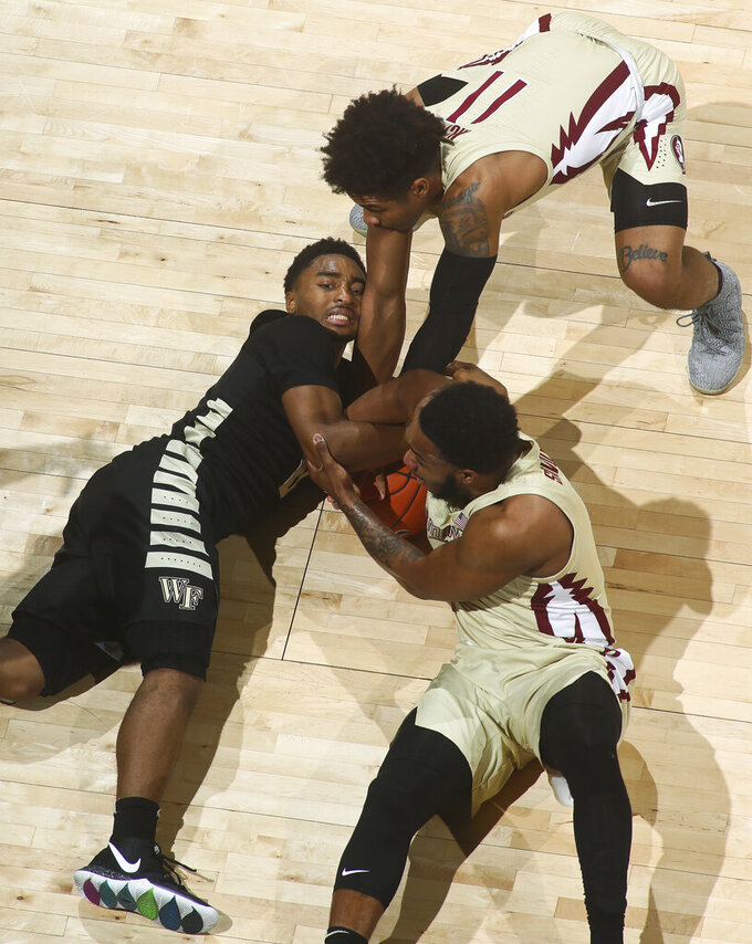 Wake Forest guard Brandon Childress, left, tries to stop Florida State guards David Nichols (11) and PJ Savoy, bottom right, from stealing the ball during the first half of an NCAA college basketball game in Tallahassee, Fla., Wednesday, Feb. 13, 2019. Florida State won 88-66. (AP Photo/Phil Sears)