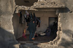 A resident of Al-Baali Street cleans a room inside her home, heavily damaged by airstrikes in Beit Hanoun, northern Gaza Strip, Friday, June 18, 2021. (AP Photo/Felipe Dana)