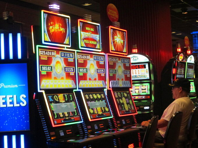 This June 23, 2021 photo shows a gambler playing a slot machine at Bally's casino in Atlantic City, N.J. Figures released on Sept. 16, 2021 show the Atlantic City casinos and the three racetracks that offer sports betting collectively won over $427 million in August, 31% more than they did in August 2020 as the casinos were just emerging from coronavirus-related closures. (AP Photo/Wayne Parry)