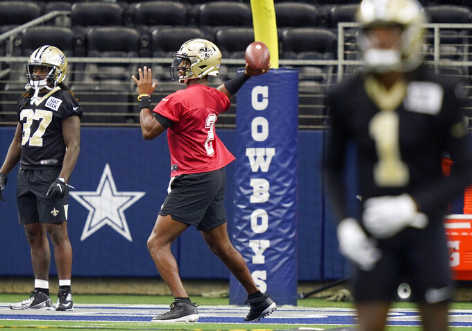 New Orleans Saints quarterback Jameis Winston (2) passes with teammates running back Tony Jones (37) looking on during NFL football practice in Arlington, Texas, Tuesday, Aug. 31, 2021. (AP Photo/LM Otero)