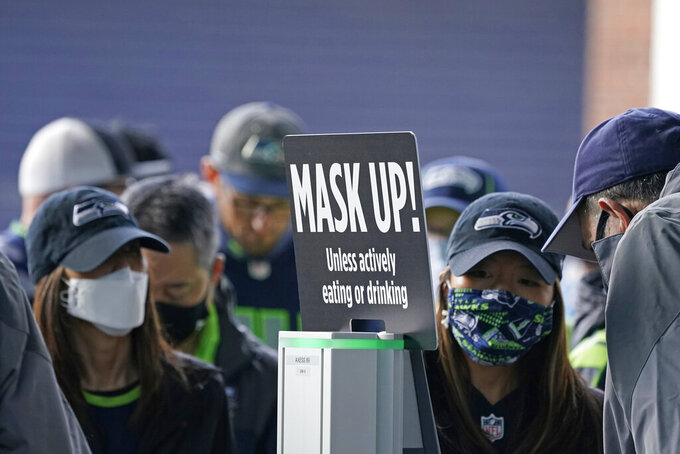 """Fans pass by a sign that reads """"Mask Up!"""" as a precaution due to the COVID-19 pandemic, before an NFL football game between the Seattle Seahawks and the Tennessee Titans, Sunday, Sept. 19, 2021, in Seattle. (AP Photo/Elaine Thompson)"""